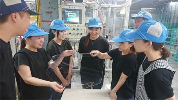ロボットで加工した製品を見て、歓声を上げる社員達